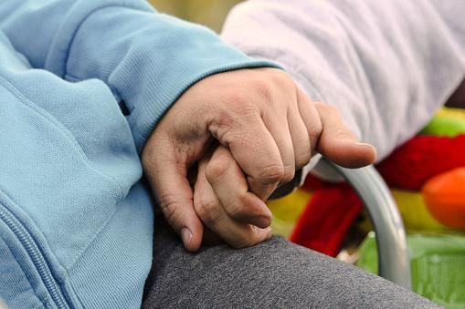 Close up of two people holding hands.