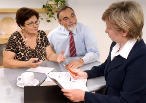 Elderly couple speaking with their estate planning attorney
