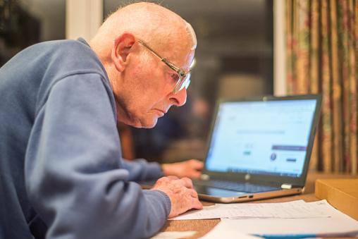 Elderly man looking over paperwork