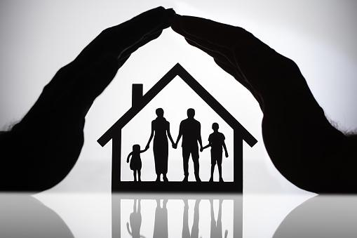 Hands covering small figures of a family inside a home